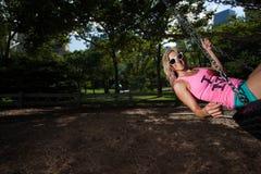Mulher atlética loura nova que senta-se em um balanço do pneu Imagens de Stock Royalty Free