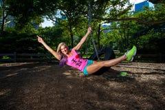 Mulher atlética loura nova que senta-se em um balanço do pneu Fotografia de Stock