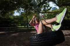 Mulher atlética loura nova que senta-se em um balanço do pneu Imagem de Stock