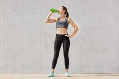 Mulher atlética na água potável do sportswear do recipiente plástico ao ter o exercício no gymnasiun, mantém a mão no quadril Cor imagens de stock