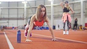 A mulher atlética na roupa que dos esportes fazer empurra levanta Uma garrafa com água perto dela vídeos de arquivo