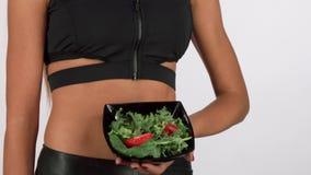 Mulher atlética no sportswear que guarda uma bacia de salada fresca video estoque