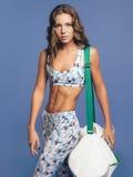 Mulher atlética nova bonita com um saco em um fundo azul Fotos de Stock Royalty Free