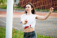 A mulher atlética nova bonita no sportswear é treinamento no estádio no fundo de um objetivo do futebol com futebol Está feliz fotografia de stock royalty free