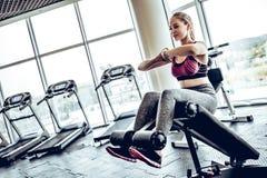 Mulher atlética nova bonita que faz algumas triturações em um banco no gym fotografia de stock royalty free