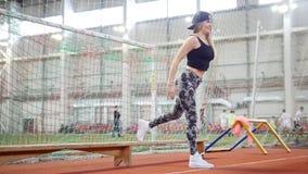 Mulher atlética nova nos leggins que fazem exercícios de pé agradáveis usando um banco video estoque