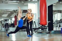 Mulher atlética nova que faz exercícios com o instrutor pessoal da aptidão imagens de stock