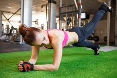 Mulher atlética nova que faz o exercício do núcleo no gym imagem de stock royalty free