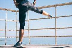 Mulher atlética nova que faz o pé que estica na praia no mo imagens de stock royalty free
