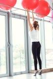 Mulher atlética nova que toma a bola vermelha da aptidão no gym imagem de stock royalty free