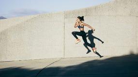 Mulher atlética que corre e que salta fora Foto de Stock Royalty Free