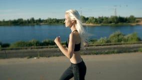 Mulher atlética que corre perto da praia Corredor fêmea que movimenta-se Exercício ao ar livre video estoque