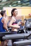 Mulher atlética que escuta a música na escada rolante Imagens de Stock Royalty Free