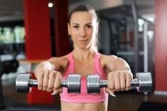 Mulher atlética que faz o exercício com pesos perto acima imagem de stock