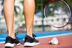 Mulher atlética que joga o badminton na corte fora imagem de stock