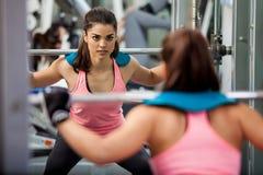 Mulher atlética que levanta um barbell Imagem de Stock