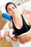 Mulher atlética séria que prende um dumbbell em casa Imagem de Stock Royalty Free