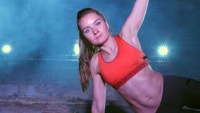 A mulher atlética, 'sexy' executa exercícios com o sistema do trx da aptidão, correias da suspensão de TRX Na noite, no fumo clar video estoque