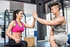 Mulher atlética do homem e do instrutor que dá uns cinco altos Imagem de Stock