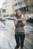 A mulher atlética, feliz que guarda a distribui para travar gotas da chuva Imagens de Stock