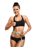 Mulher atlética que mede sua cintura e que mostra a polegar o isolado ascendente Fotografia de Stock