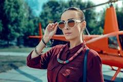 Mulher atraente séria que toma em óculos de sol grandes ao ter a joia imagens de stock
