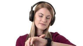 A mulher atrativa bonita com fones de ouvido escuta a música no smartwatch Fundo branco isolado filme