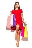Mulher atrativa bonita com os sacos shoping da cor nas mãos no fundo branco verão Foto de Stock