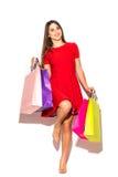 Mulher atrativa bonita com os sacos shoping da cor nas mãos no fundo branco verão Fotos de Stock Royalty Free