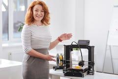 Mulher atrativa bonita que mostra lhe uma impressora 3d Fotografia de Stock Royalty Free