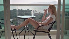 Mulher atrativa bonita que senta-se na cadeira do balcão que relaxa apreciando a vista Água bebendo filme