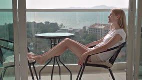 Mulher atrativa bonita que senta-se na cadeira do balcão que relaxa apreciando a vista Árvores do mar de turquesa video estoque