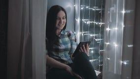 Mulher atrativa bonita que usa o PC da tabuleta e sentando-se na soleira decorada com festões, uma comunicação de Skype vídeos de arquivo
