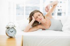 Mulher atrativa cansado que estica para fora o encontro em sua cama Imagem de Stock Royalty Free