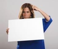A mulher atrativa com cabelo longo faz certamente gestos ao guardar um sinal branco imagem de stock