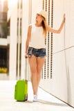 Mulher atrativa com a mala de viagem que relaxa após a chegada imagens de stock