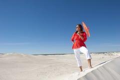 Mulher atrativa com o guarda-chuva na duna de areia do deserto Imagens de Stock