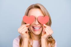 Mulher atrativa com o sorriso de irradiação que tem dois corações vermelhos pequenos Fotos de Stock Royalty Free