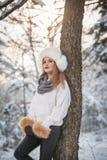 Mulher atrativa com o tampão e o revestimento brancos da pele que aprecia o inverno Ideia lateral do levantamento louro elegante  imagens de stock royalty free