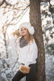 Mulher atrativa com o tampão e o revestimento brancos da pele que aprecia o inverno Ideia lateral do levantamento louro elegante  fotografia de stock royalty free