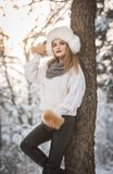 Mulher atrativa com o tampão e o revestimento brancos da pele que aprecia o inverno Ideia lateral do levantamento louro elegante  fotografia de stock