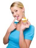 A mulher atrativa come o creme branco doce Imagens de Stock Royalty Free