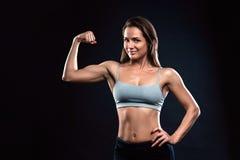 A mulher atrativa da aptidão está mostrando seu bíceps no fundo preto foto de stock