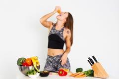 A mulher atrativa da aptidão, treinou o halterofilista seguro atlético da jovem mulher do poder fêmea do ajuste que come a laranj foto de stock