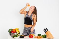 A mulher atrativa da aptidão, treinou o halterofilista seguro atlético da jovem mulher do poder fêmea do ajuste que come a laranj fotos de stock