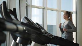 A mulher atrativa da Idade Média está correndo no moinho do passo no gym do esporte vídeos de arquivo