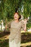 Mulher atrativa de meia idade que ri alto nos ramos da folha das árvores fotografia de stock
