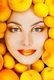 Mulher atrativa de sorriso com os pêssegos e o abricó frescos grandes maduros Foto de Stock Royalty Free