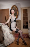A mulher atrativa de sorriso feliz que vestem um vestido elegante e as meias pretas que sentam-se no sofá armam-se Menina sensual Imagem de Stock Royalty Free