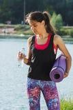 A mulher atrativa desportiva nos lagos costeia com uma esteira Fotografia de Stock